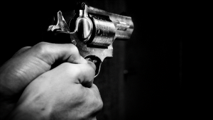 Image of two hands holding a cocked revolver.
