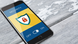 Image of a mobile device resting on a wood surface and showing cybersecurity features enabled on the device.