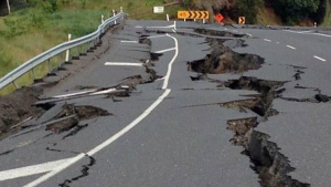 Image of a broken up paved road, badly  damaged by an earthquake.