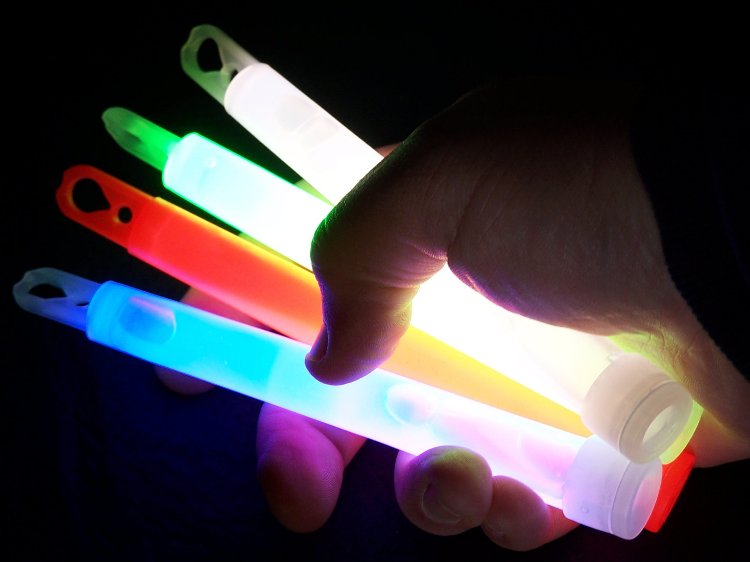A hand in the dark holding four different colored, glowing light sticks.
