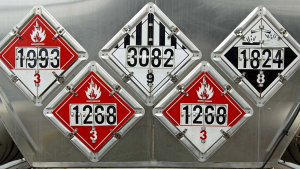 Image of the back end of a tanker trailer with five hazardous materials placards.