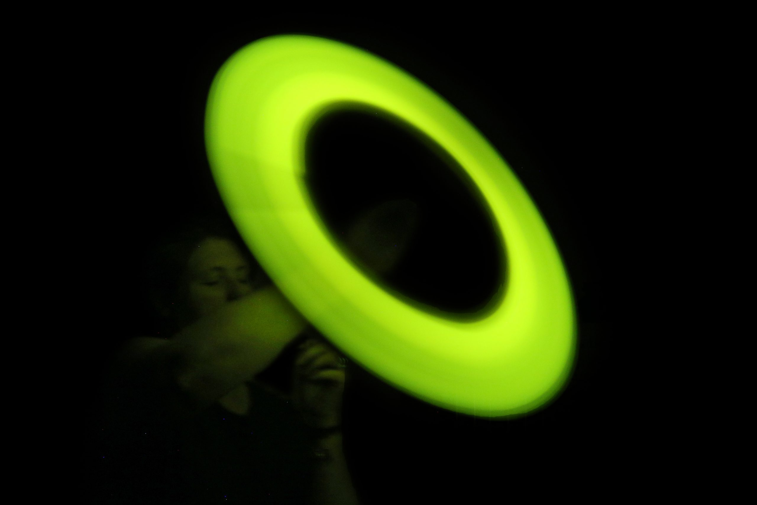A glowing light stick being swung in a circle on a string creating the illusion of a large, glowing circle.