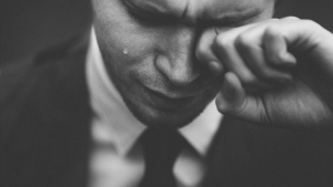 Image of a distraught man wiping his left eye with his left hand.