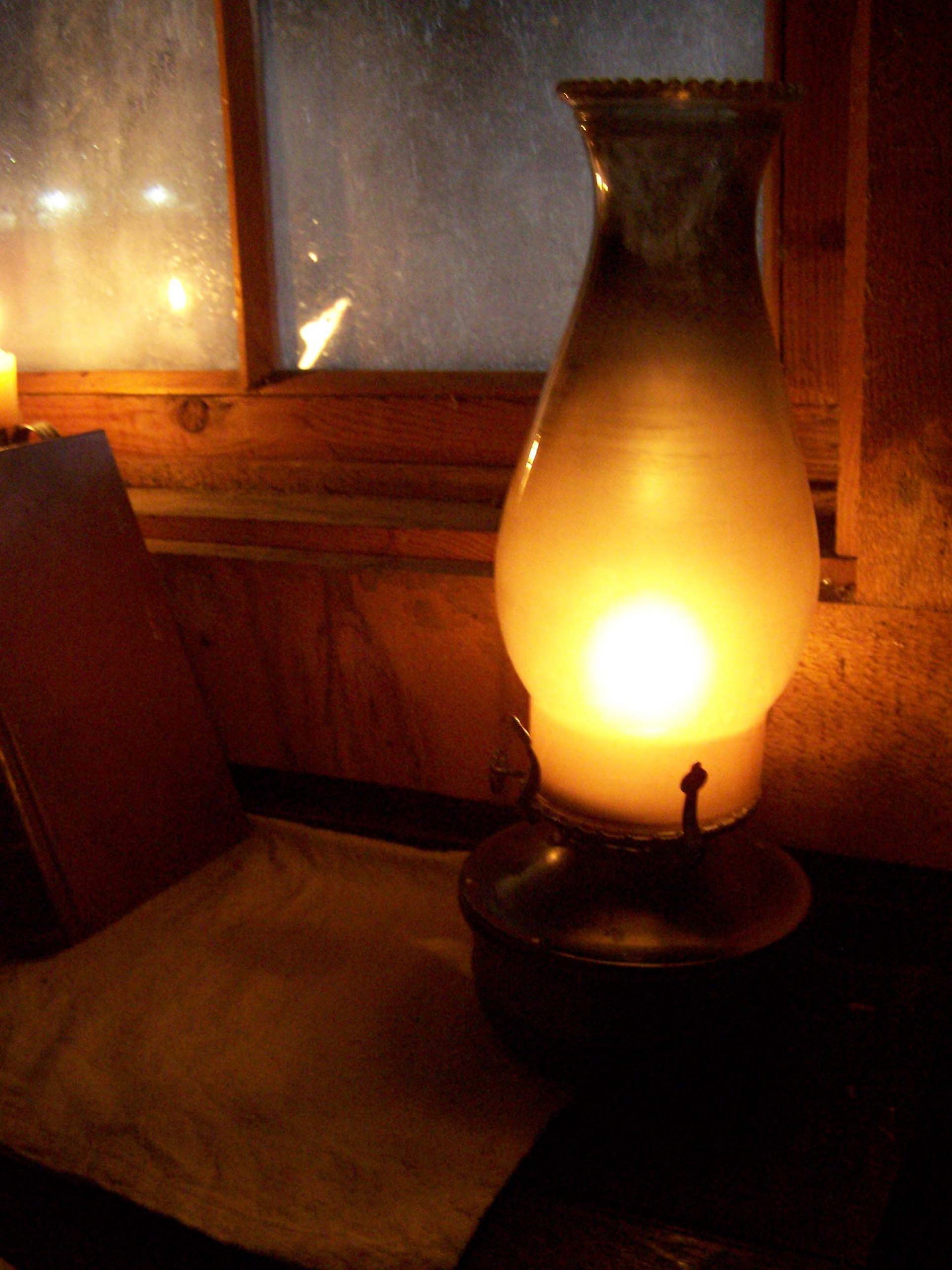 A lighted oil lamp sitting next to a window.