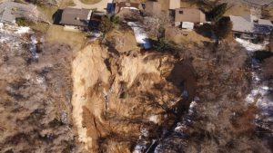 Aerial view image of a landslide pushing against some houses.