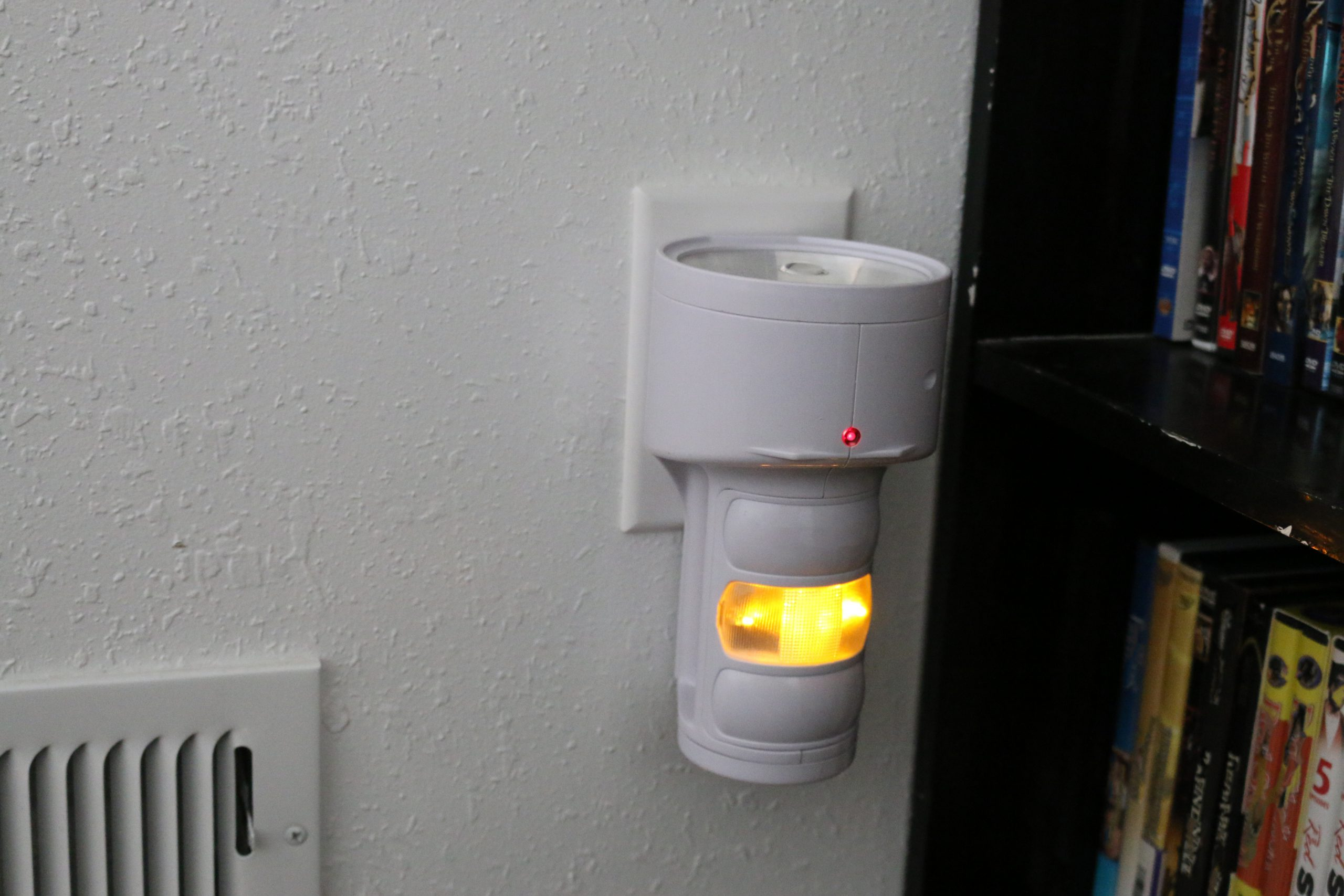 Emergency flashlight plugged into wall electrical outlet.