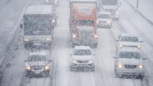 Image of snow falling on multiple cars and trucks slowly driving or stopped on a slick freeway.