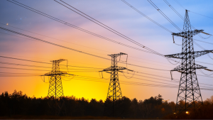 Image of three different power lines and poles with the sun setting in the background.