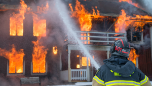 Image of a firefighter using a fire hose to spray water onto a burning two-story house.